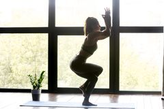 Jonge sportieve vrouw die de oefening van yogaeagle doen stock afbeelding
