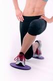 Jonge sportieve vrouw die glijdende bewegingsschijven gebruiken Royalty-vrije Stock Foto
