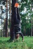 Jonge sportieve vrouw die handstand doen die rechte benen bij boom het praktizeren in het hout leunen Royalty-vrije Stock Fotografie