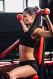 Jonge sportieve vrouw die oefeningen met domoren in de gymnastiek doen Stock Fotografie