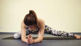 Jonge sportieve vrouw die uit het volledige lichaam uitrekken terwijl status in een yogaasana die sterke wapens vereist stock video