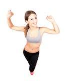 Jonge sportieve vrouw het uitrekken zich wapens met dichtgeklemde vuisten Royalty-vrije Stock Foto's