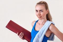 Jonge sportieve vrouw met gerolde yogamat en handdoek De ruimte van het exemplaar stock afbeelding