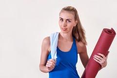 Jonge sportieve vrouw met gerolde yogamat en handdoek De ruimte van het exemplaar stock afbeeldingen