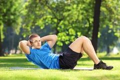 Jonge sportman die abs in een park uitoefenen stock afbeeldingen
