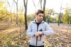 Jonge sportman in openlucht in park het luisteren muziek met oortelefoons drinkwater die horloge bekijken stock afbeelding