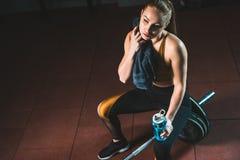 Jonge sportvrouw afvegende hals door handdoek en het zitten op barbell stock fotografie