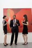 Jonge stafmedewerkers die een gesprek voor het schilderen in kunstgalerie hebben stock foto