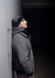 Jonge stedelijke mens in de winterkleren die zich in donkere passage bevinden Stock Foto's