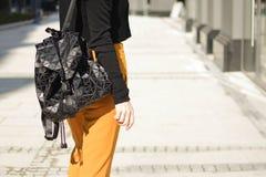 Jonge stedelijke vrouw met manier en moderne zwarte rugzak en oranje broek in de straat van Europese stad stock afbeeldingen