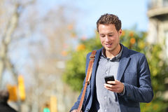 Jonge stedelijke zakenmanberoeps op smartphone
