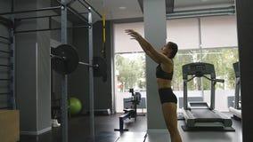Jonge sterke vrouw met perfect geschiktheidslichaam in sportkleding die met geneeskundebal bij gymnastiek uitoefenen Meisje die c stock footage