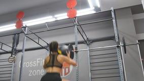 Jonge sterke vrouw met perfect geschiktheidslichaam in sportkleding die met geneeskundebal bij gymnastiek uitoefenen Meisje die c stock video