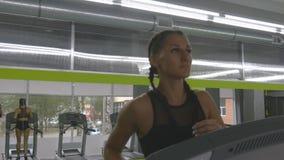Jonge sterke vrouw met perfect geschiktheidslichaam in sportkleding die op tredmolen in gymnastiek lopen Meisje die tijdens cardi stock videobeelden