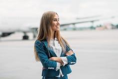 Jonge stewardess in eenvormig op vliegtuigenparkeren stock afbeelding