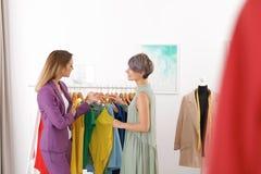Jonge stilist die cliënt helpen om in kleren te kiezen royalty-vrije stock afbeeldingen