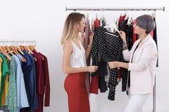 Jonge stilist die cliënt helpen om in kleren te kiezen royalty-vrije stock foto