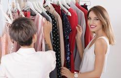 Jonge stilist die cliënt helpen om in kleren te kiezen royalty-vrije stock foto's