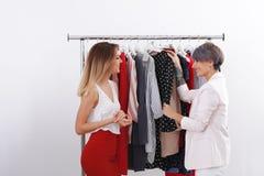 Jonge stilist die cliënt helpen om in kleren te kiezen stock afbeeldingen