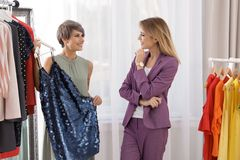 Jonge stilist die cliënt helpen om in kleren te kiezen royalty-vrije stock fotografie