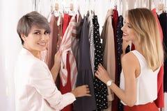Jonge stilist die cliënt helpen om in kleren te kiezen stock afbeelding