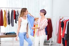 Jonge stilist die klant helpen om kleren te kiezen stock foto's