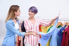 Jonge stilist die klant helpen om kleren te kiezen royalty-vrije stock foto