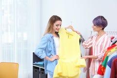 Jonge stilist die klant helpen om kleren te kiezen royalty-vrije stock afbeeldingen