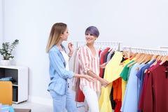 Jonge stilist die klant helpen om kleren te kiezen stock fotografie
