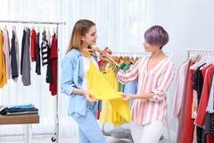 Jonge stilist die klant helpen om kleren te kiezen stock foto