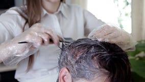 Jonge stilist, kapper die haarkleur toepassen op een vrouw Haar het kleuren in donkere kleur, proces stock videobeelden