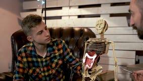 Jonge student die aan zijn leraar luisteren die de structuur van menselijk lichaamsorganen explaning stock footage
