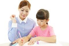 Jonge student die met leraar bestuderen stock foto's