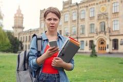 Jonge student die met rugzak bij universitaire campus met notitieboekjes lopen die betrokken smartphone gebruiken stock foto