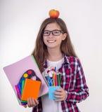 Jonge student die in oogglazen school of bureaulevering houden: pennen, notitieboekjes, schaar en appel Terug naar hogeschool of  royalty-vrije stock fotografie
