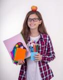 Jonge student die in oogglazen school of bureaulevering houden: pennen, notitieboekjes, schaar en appel Terug naar hogeschool of  stock fotografie
