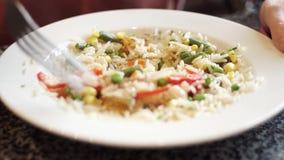 Jonge student die rijst eten, die de ingrediënten mengen met een vork Zeer close-upschot stock videobeelden