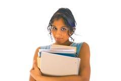 Jonge student die zich met een stapel boeken bevindt Stock Foto's