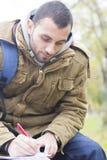 Jonge student die in zijn notaboek schrijven Stock Foto's