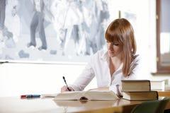 Jonge student in een bibliotheek Stock Afbeelding