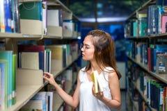 Jonge Student Girl Finding Book in Klaslokaal stock foto's