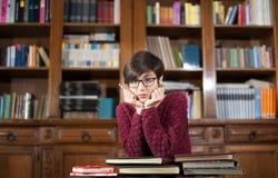 Jonge studente die in de bibliotheek wordt vermoeid stock foto