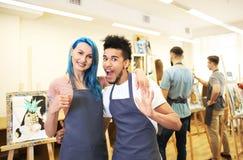 Jonge studenten die duim-op gebaar in kunstacademie tonen royalty-vrije stock afbeeldingen