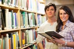 Jonge studenten die een boek houden Stock Foto