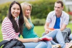 Jonge studenten die in het park zitten Stock Afbeelding