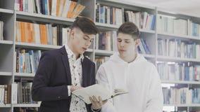 Jonge studenten die met boeken aan examen in bibliotheek voorbereidingen treffen stock footage