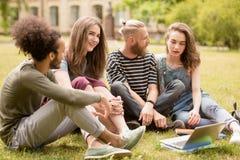 Jonge studenten die op wetten in Universitair park ontspannen Stock Afbeeldingen