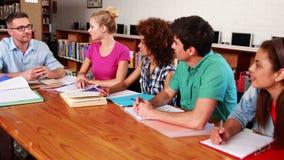 Jonge studenten die samen in de bibliotheek met hun leraar bestuderen stock videobeelden