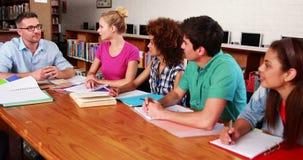 Jonge studenten die samen in de bibliotheek met hun leraar bestuderen stock footage