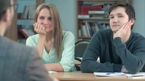 Jonge studenten tijdens het luisteren een interessante lezing stock videobeelden